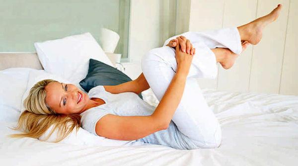 Женщина выполняет зарядку в постели