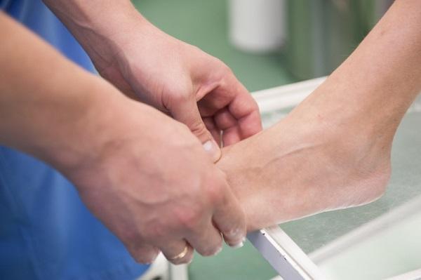 Специалист осматривает стопу пациента