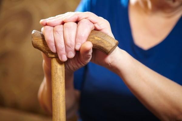 Женщина держит костыль