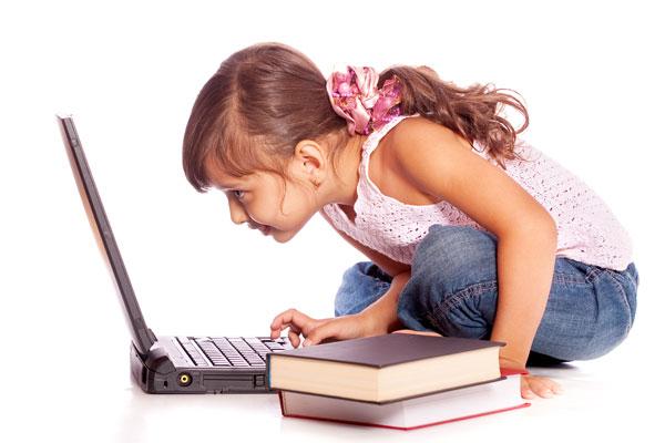 Девочка сидит согнувшись перед ноутбуком