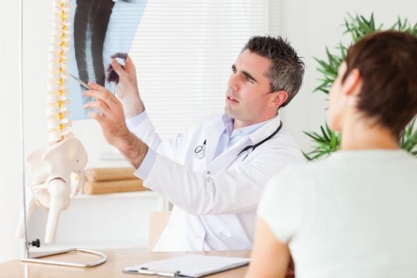 Доктор осматривает рентген позвоночника