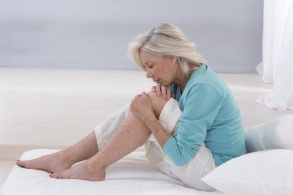 Женщина испытывает боли в колене