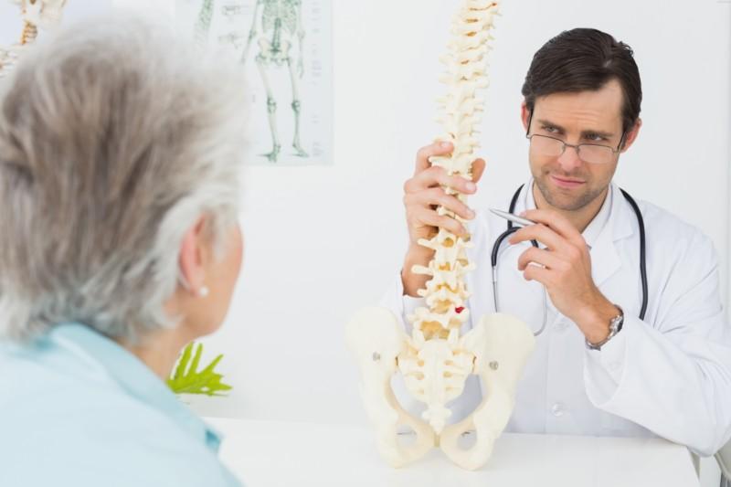 Доктор показывает макет позвоночника