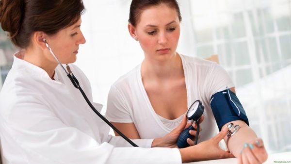 Доктор измеряет давление женщине