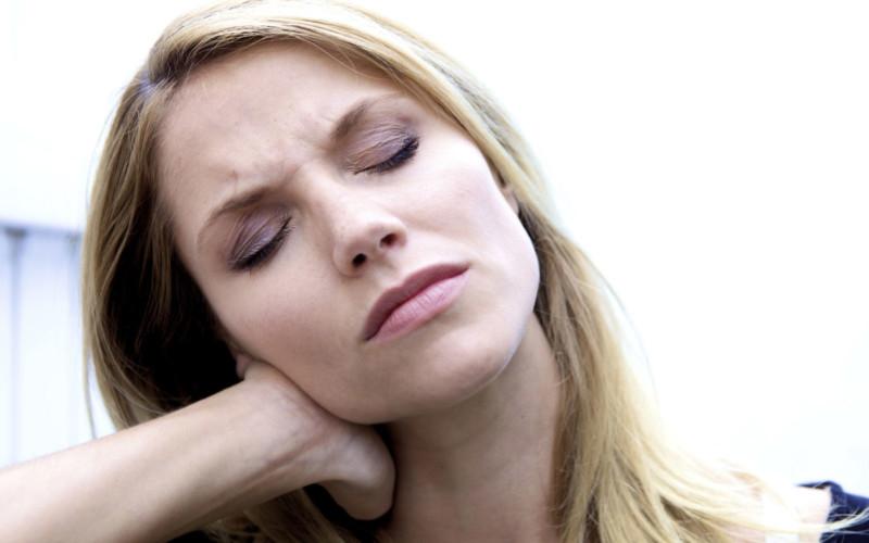 Женщина страдает от боли в шее