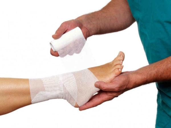 Специалист бинтует ногу